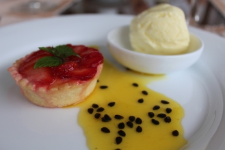 Strawberry tart amidst a passionfruit drizzle.